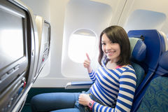 Happy woman sitting in airplane royalty free stock photo