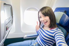 Happy woman sitting in airplane Royalty Free Stock Images