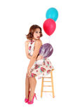 Happy woman sitting with balloons. A beautiful young woman siting on a chair, holding Stock Photos