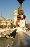 Happy woman sitting on the balustrade of a bridge Stock Images
