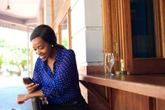 Happy woman sitting at bar smiling with mobile phone Royalty Free Stock Images