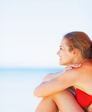 Happy woman sitting on beach and looking on copy space Stock Images