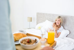 Happy woman sitting in bed with breakfast in foreground Stock Images
