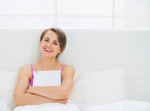 Happy woman sitting on bed and embracing tablet PC Royalty Free Stock Images