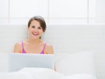 Happy woman sitting on bed and working on laptop Stock Image