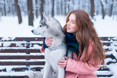 Happy woman sitting on the bench with husky Stock Photos