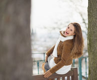 Happy woman sitting on bench in winter outdoors Royalty Free Stock Photo