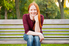 Happy Woman Sitting on a Bench Stock Image