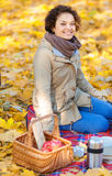 Happy woman sitting on the blanket. Full of joy. Pleasant delighted young woman sitting on the blanket and smiling while having picnic Stock Images