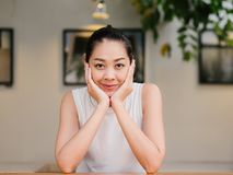 Happy woman is sitting in the cafe with a smile in her face. Happy Asian woman is sitting in the cafe with a smile in her face stock image