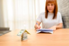 Happy woman sitting and calculating bills in the home office.Money house from dollar banknote on wooden table. stock images