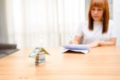 Happy woman sitting and calculating bills in the home office.Money house from dollar banknote on wooden table. stock photo