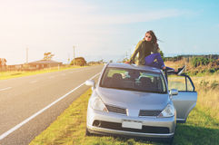 Happy woman sitting on car roof Stock Photography