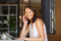 Happy woman sitting at city bar with mobile phone and tablet Royalty Free Stock Image