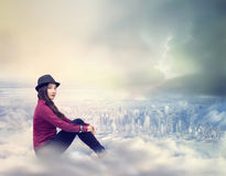 Happy Woman Sitting on the Clouds. Happy Young Woman Sitting on the Clouds Above the City Stock Photos