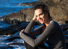 Happy woman sitting on the coast Royalty Free Stock Photography