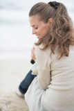 Happy woman sitting on cold beach. rear view Royalty Free Stock Image