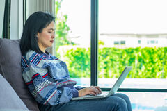 Happy woman sitting on comfortable sofa using laptop near window Royalty Free Stock Photos