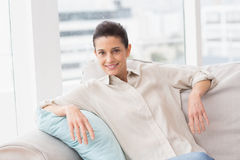 Happy woman sitting comfortably on sofa Stock Photo