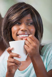 Happy woman sitting on couch having coffee Stock Photography