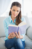 Happy woman sitting on couch holding book Royalty Free Stock Photos