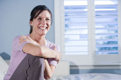 Happy woman sitting on couch smiling royalty free stock images