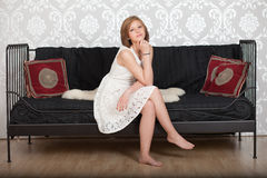 Happy woman sitting on a couch Stock Images