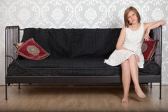 Happy woman sitting on a couch Royalty Free Stock Photo