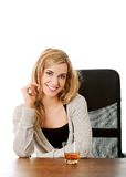 Happy woman sitting at the desk with cup of tea Royalty Free Stock Photos