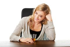 Happy woman sitting at the desk with cup of tea Stock Images