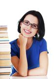 Happy woman sitting at a desk with stack of books Royalty Free Stock Photo