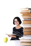 Happy woman sitting at a desk with stack of books Stock Images