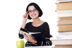 Happy woman sitting at a desk with stack of books Royalty Free Stock Image