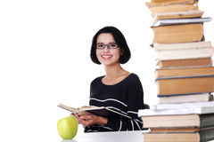 Happy woman sitting at a desk with stack of books Royalty Free Stock Images