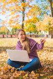 Happy Woman Sitting on Dried Leaves with Laptop Stock Photos