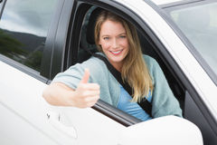Happy woman sitting in drivers seat thumb up Stock Image
