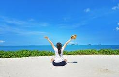 Happy woman sitting enjoy life on beach. Happy woman sitting arms outstretched back and enjoy life on the beach at Sea Stock Image