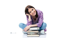 Happy woman sitting on the floor with books. Over white background and looking at camera Stock Photography