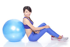 Happy woman sitting on floor with fit ball Stock Image