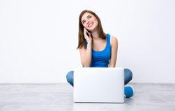 Happy woman sitting on the floor with laptop Stock Photography