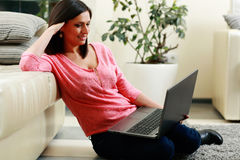 Happy woman sitting on the floor and using laptop Stock Photo
