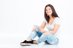 Happy woman sitting on the floor and using tablet computer Royalty Free Stock Photography