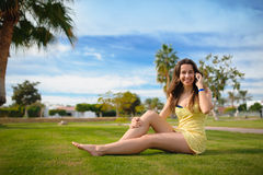Happy woman sitting on the grass and talking on the phone Royalty Free Stock Photography