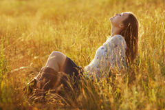 Happy woman sitting in the grass Stock Photography