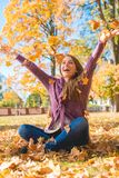 Happy Woman Sitting on Ground Playing Dry Leaves Royalty Free Stock Photography