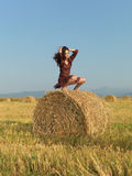 Happy woman sitting on a hay stack Stock Image