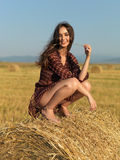 Happy woman sitting on a hay stack Stock Images