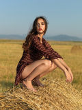 Happy woman sitting on a hay stack Stock Photography