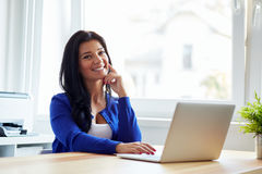 Happy woman sitting at her desk working with notebook royalty free stock images
