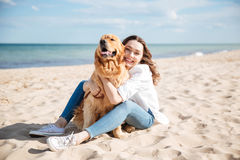 Happy woman sitting and hugging her dog on the beach Stock Photos